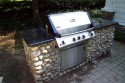 Fieldstone with granite top surrounds a grill with a side burner