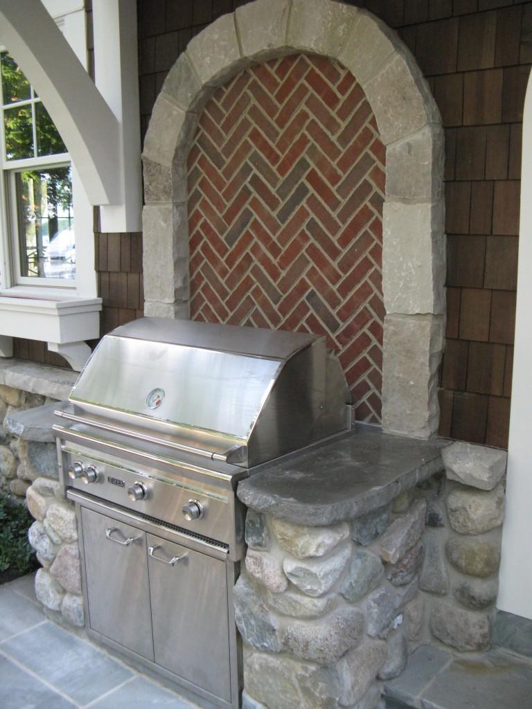 Brick backed fieldstone grill area with custom concrete countertops
